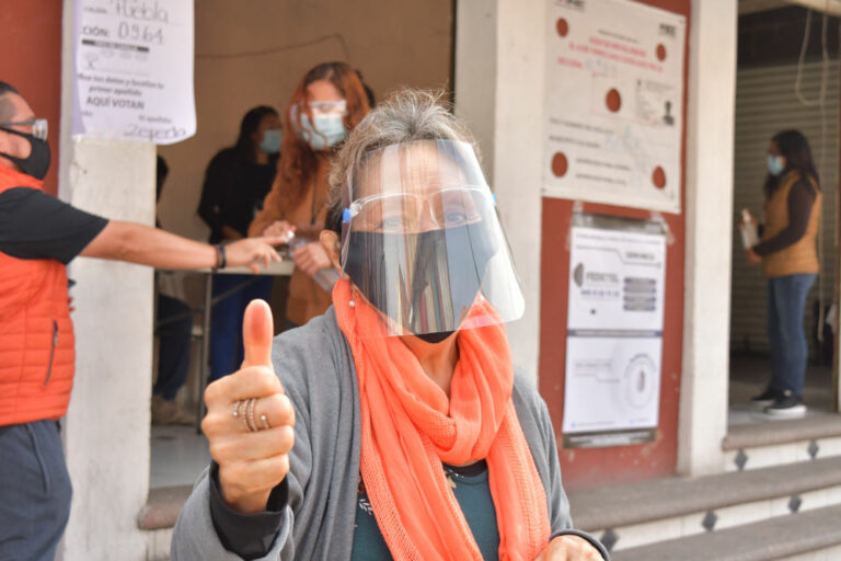 Mujer saluda mostrando dedo pulgar marcado con tinta luego de votar en Puebla, México, durante las Elecciones Intermedias del 6 de junio de 2021.