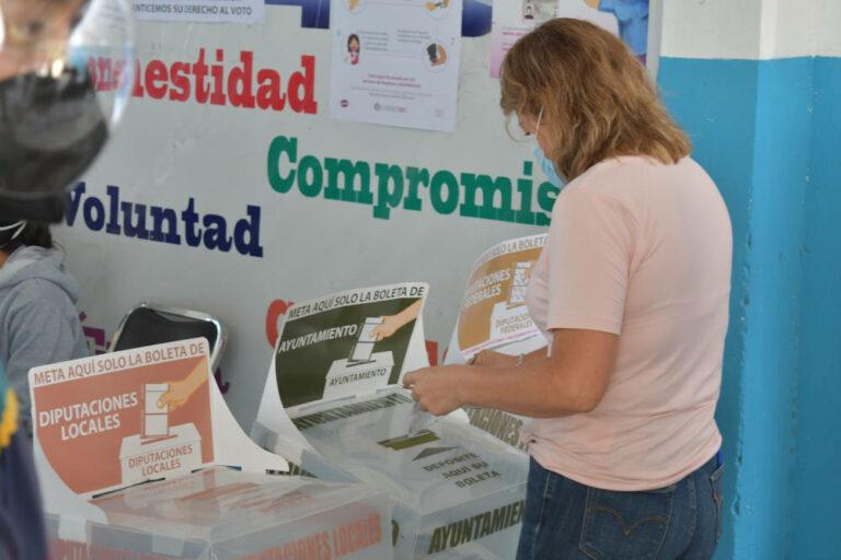 Mujer deposita boleta electoral durante Elecciones Intermedias en Puebla, México. 6 de junio de 2021.